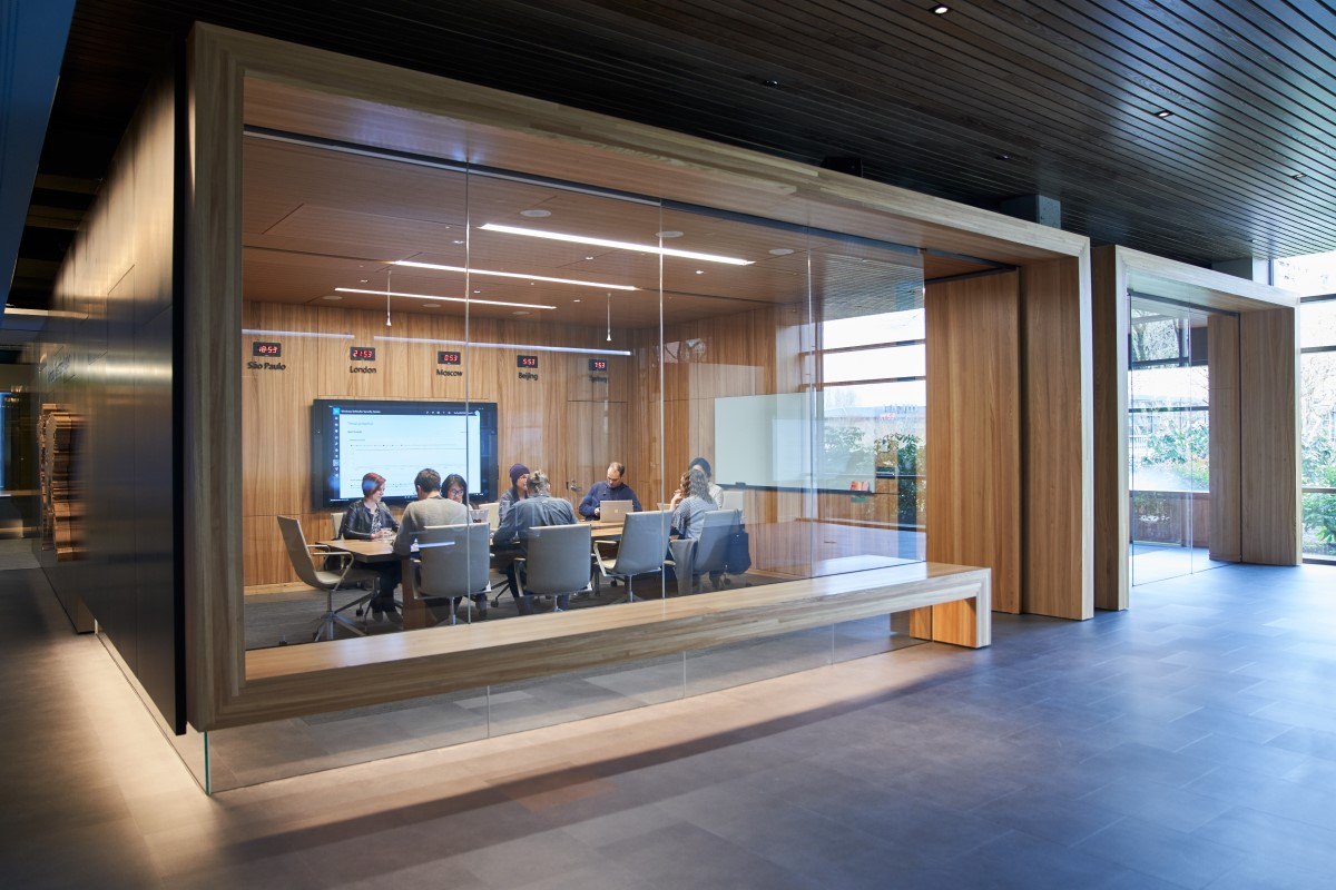 Outside of a conference room or board room meeting including people sitting around table in a room with international time clocks.