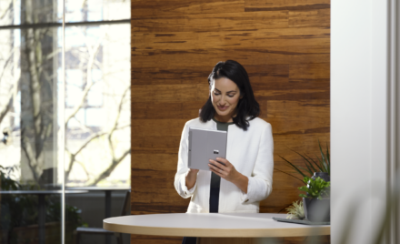 Adult female holding a platinum Surface Go 3 in tablet mode while in an office setting.