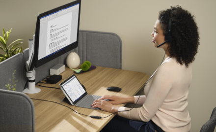 Adult female wearing Microsoft Modern USB-C Headset sitting at a desk while working on a Surface Go 3 with Surface Go Typecover in laptop mode with Microsoft Edge displayed. Microsoft Word is being presented on the large monitor.