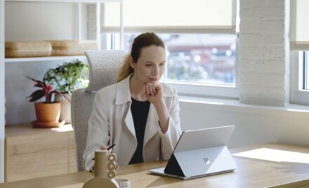 Adult female sitting at a desk, holding a Microsoft Slim Pen 2 while looking onto a platinum Surface Laptop Studio in stage mode.
