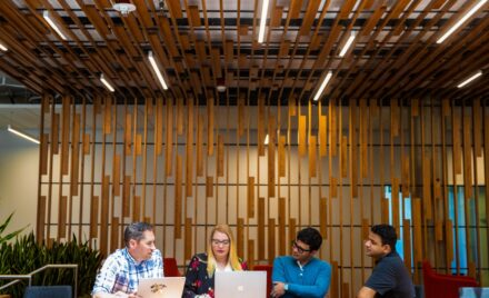 A group of tech workers hold meeting in common space of U.S. office.
