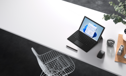 Horizontal format of an attract image of Surface Pro 7+ in laptop mode with black typepad on a desk. Windows 11 screen shown.