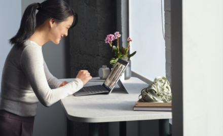 Adult female standing at her desk collaborating via Microsoft Teams video call on a Surface Pro 8 in laptop mode working on a Surface Pro Signature Keyboard.