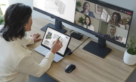 Adult female is collaborating on a Microsoft Teams video call presented on the right monitor, while Revit is in use on the left.