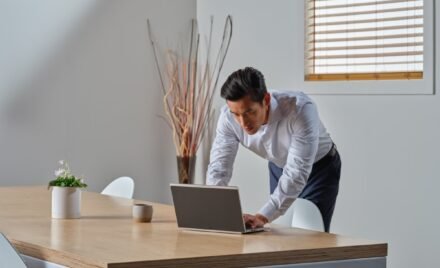 Business person leans over desk to use Acer Porsche RS laptop in a conference room.