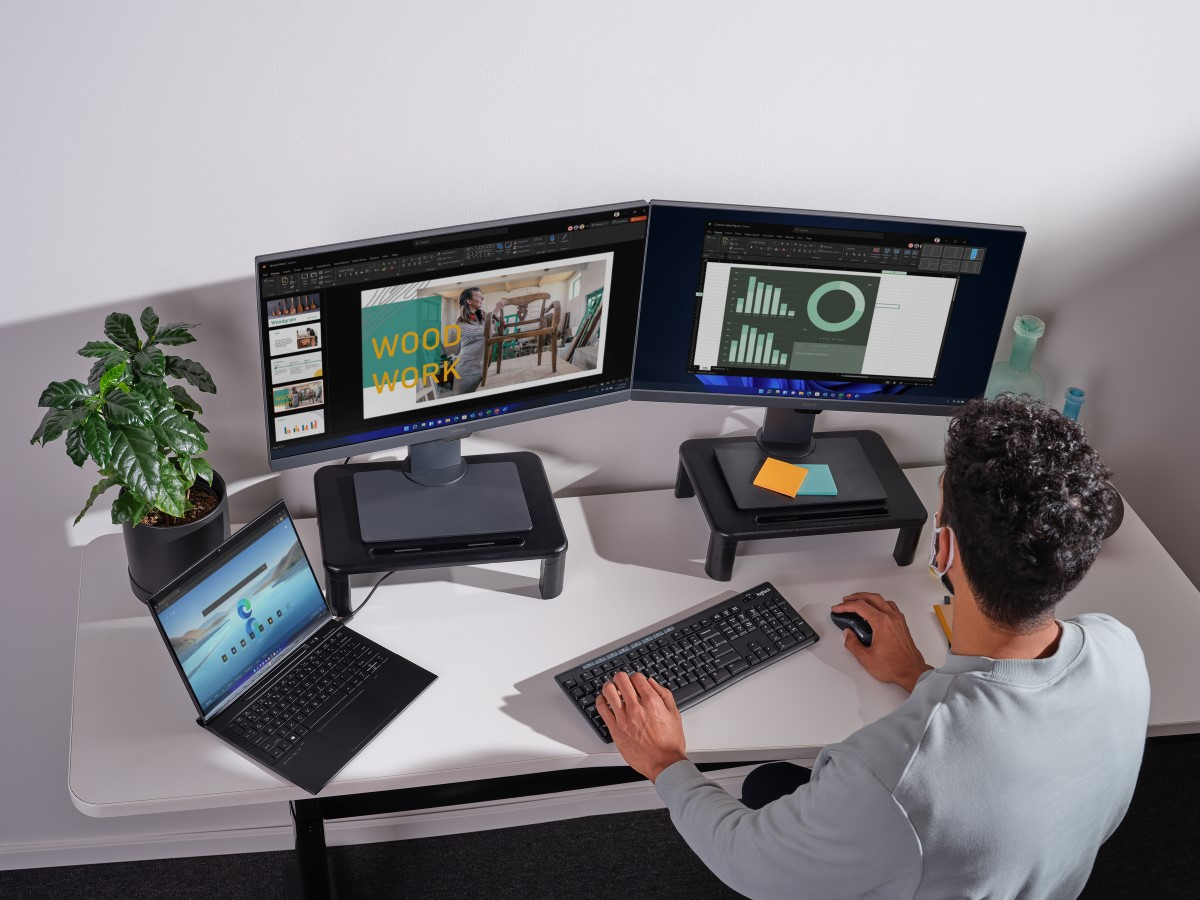 Adult male sitting in home office working on multiple screens.