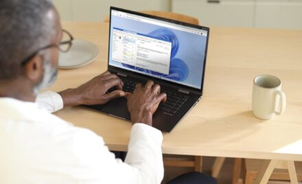 Man sitting at a wooden table typing on a laptop while using Microsoft Teams within Windows 365. Shown on Windows 11.