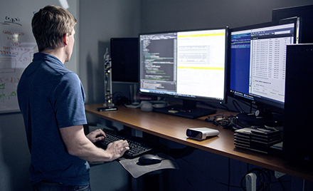 A tech worker uses a dual screen PC workstation.