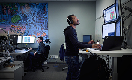 Image of a tech worker looking at a computer monitor.