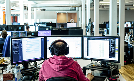 Image of a tech worker working on three monitors.