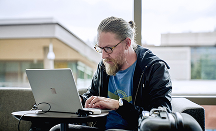 Image of a man working at a laptop.
