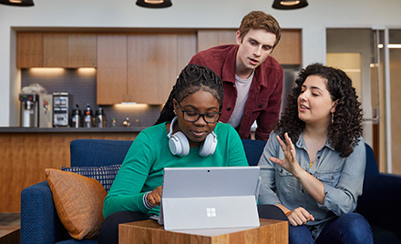 Image of students hovered over a computer.
