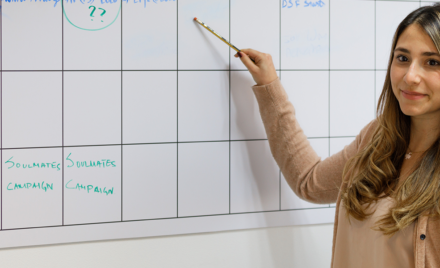 Image of a developer pointing at a square on a whiteboard.