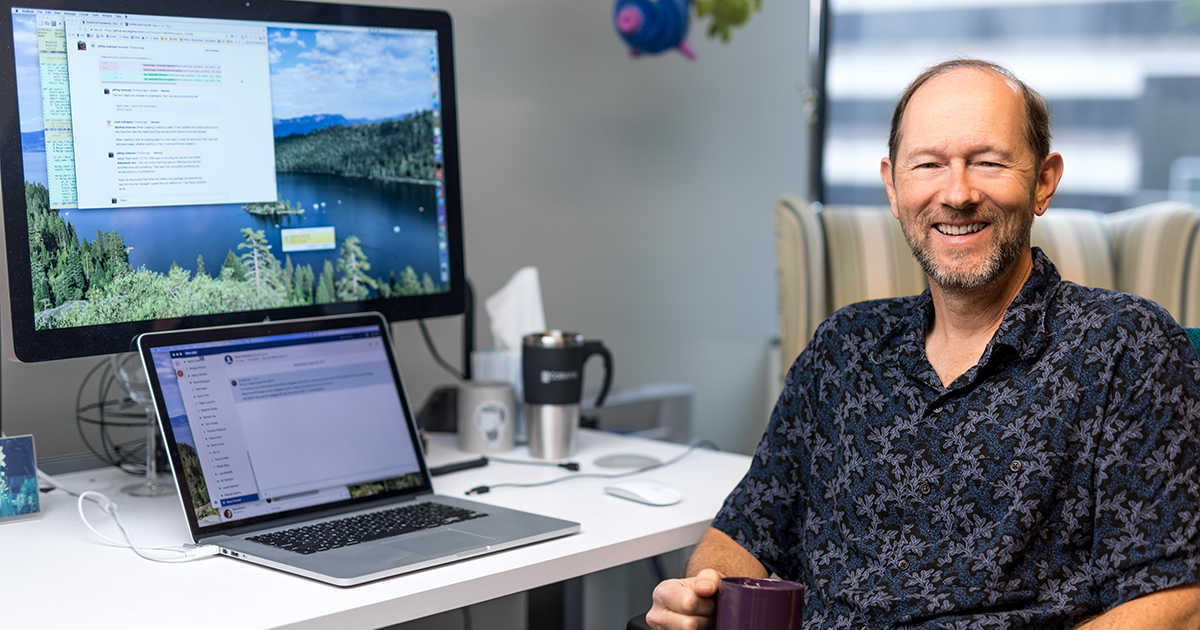 Image of a developer sitting with a cup of coffee at his desk.