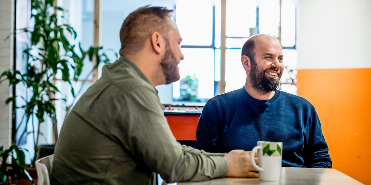 Two workers sit smiling at a table, over a cup of coffee.