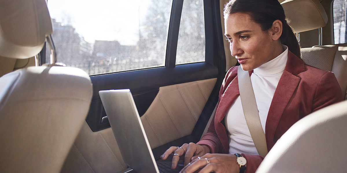 A woman in a car types on her laptop.