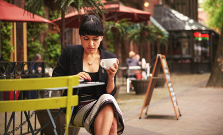 Image of a worker holding a cup of coffee and checking her phone.