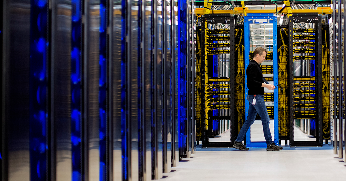 Image of a worker walking through a datacenter.