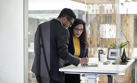 Image of two coworkers collaborating beside a standing desk.