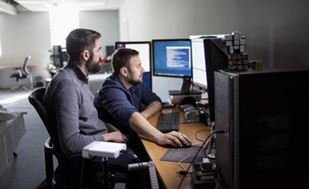 Image of two workers collaborating on a desktop PC.
