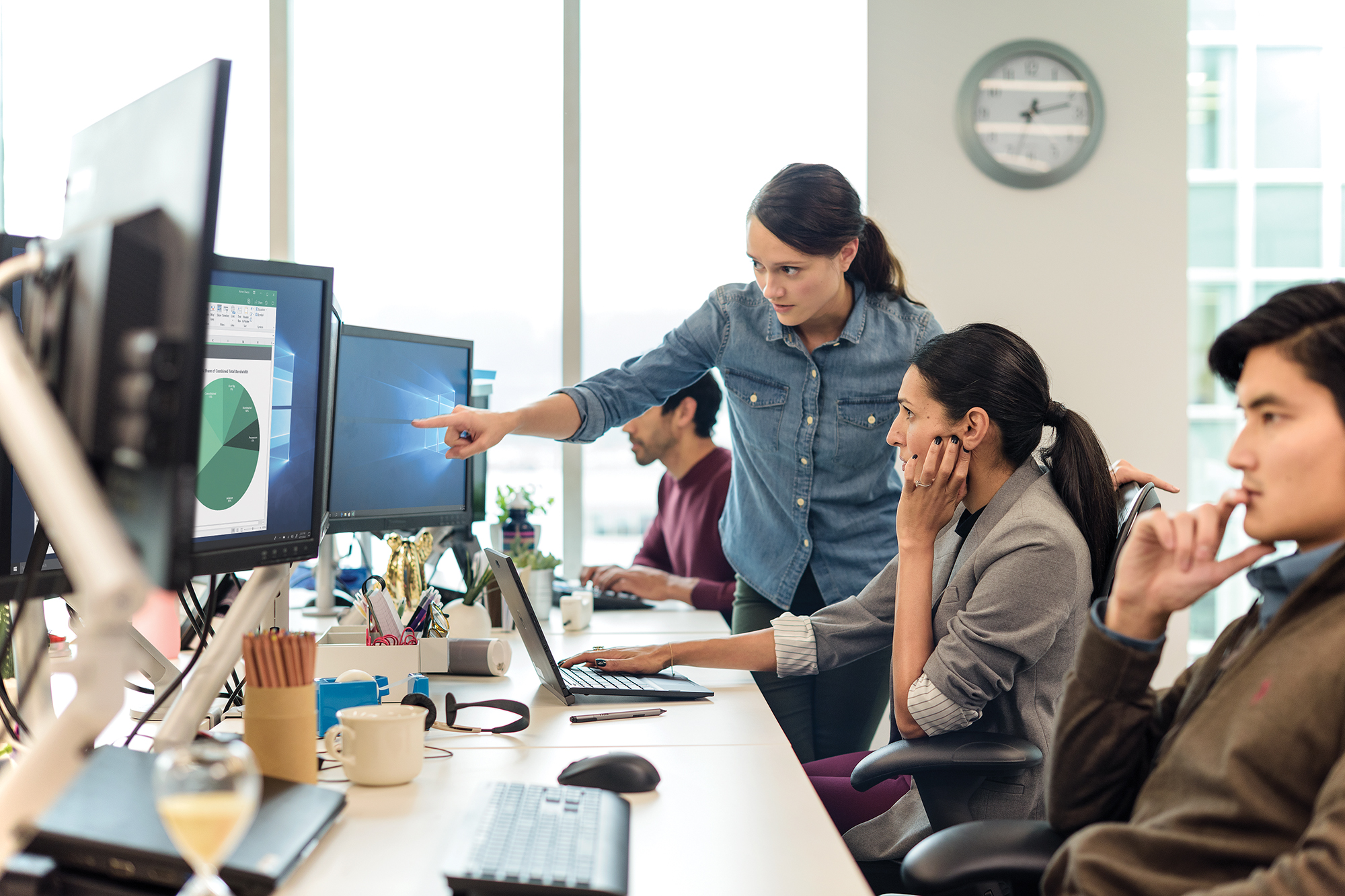 Image of coworkers pointing at a computer monitor.