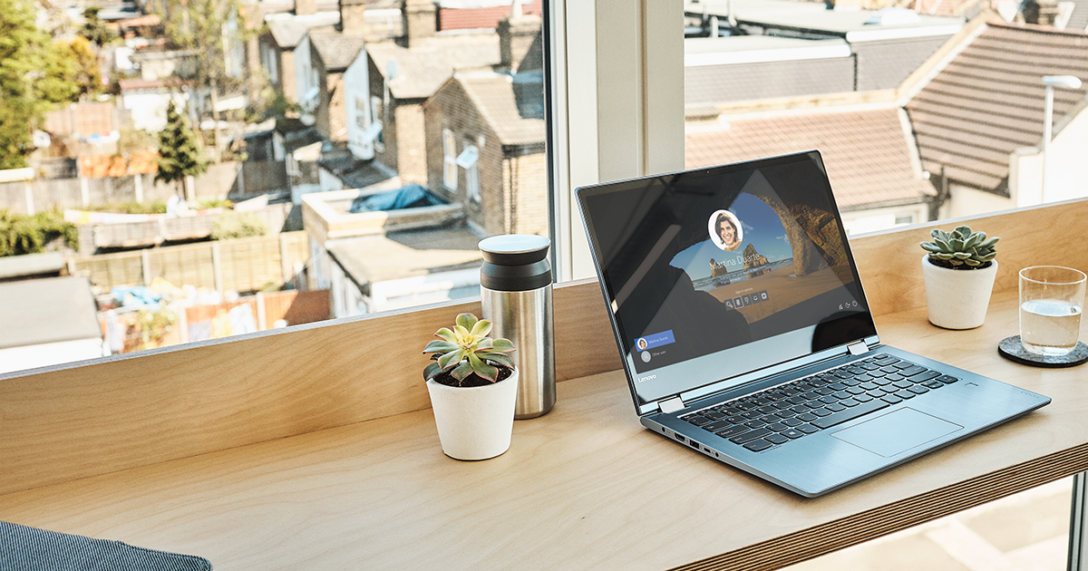 Image of a laptop open on a countertop, a cityscape in the distance.