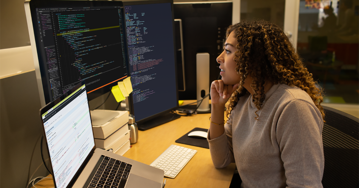 Real people, real offices. Female developer coding at her desk.