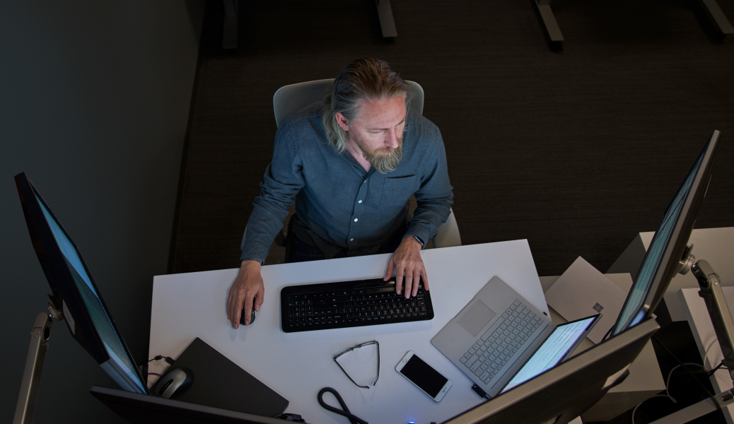 Top-down view of a bearded man in a gray/blue shirt seated at a desk working on a Surface laptop