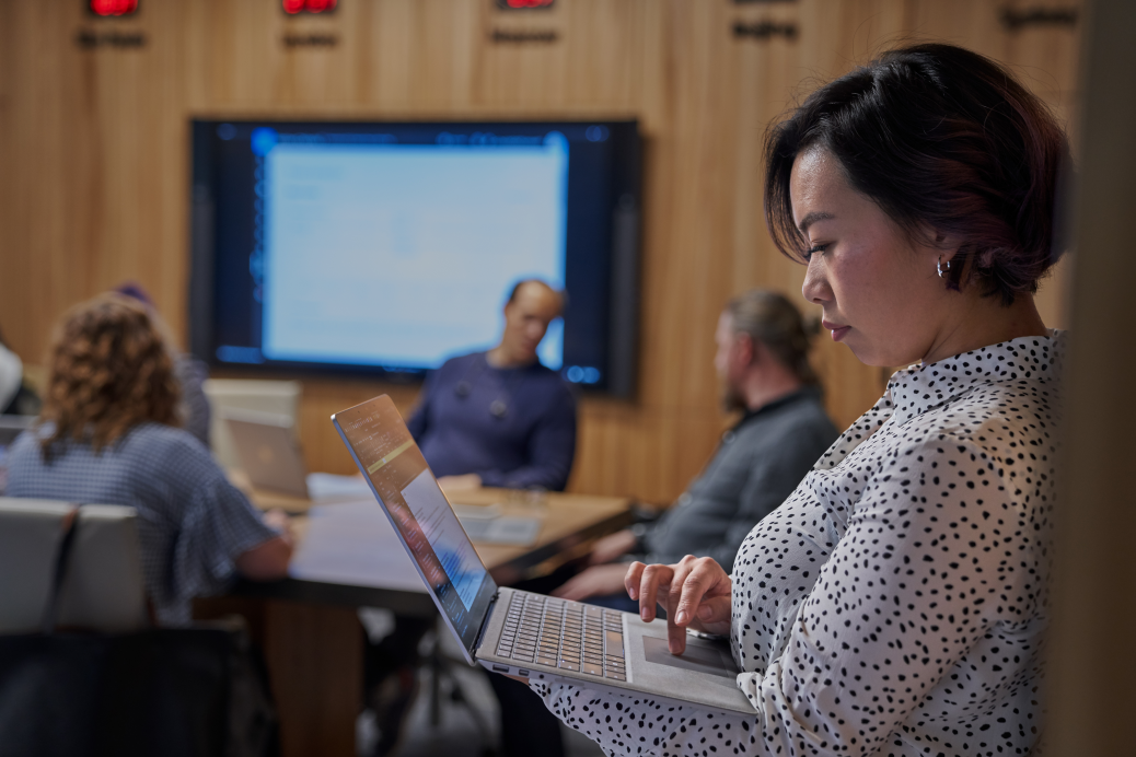 Women looking at Surface laptop with background of a conference room.