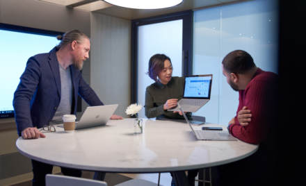 Woman and two men working in a meeting room all with Surface laptops.