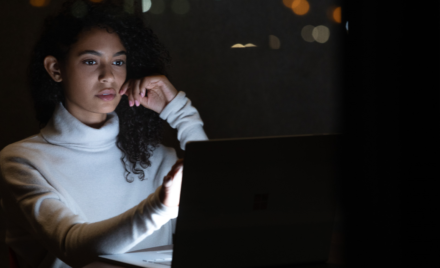 Commercial contextual lifestyle image of adult female working on Surface Book 3 in dark office.