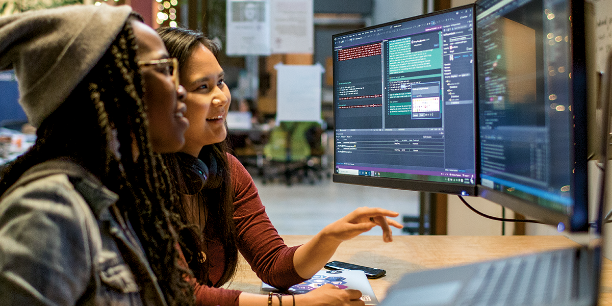 Two female developers working and collaborating in an enterprise office.