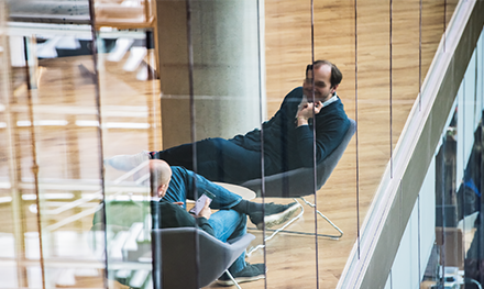 Image of two executives in the tech industry chat while seated in common area of UK office.
