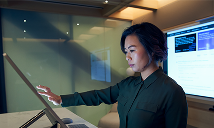 An image of a woman wearing a dark shirt in a dim office scrolling or working on a Microsoft Surface Studio.