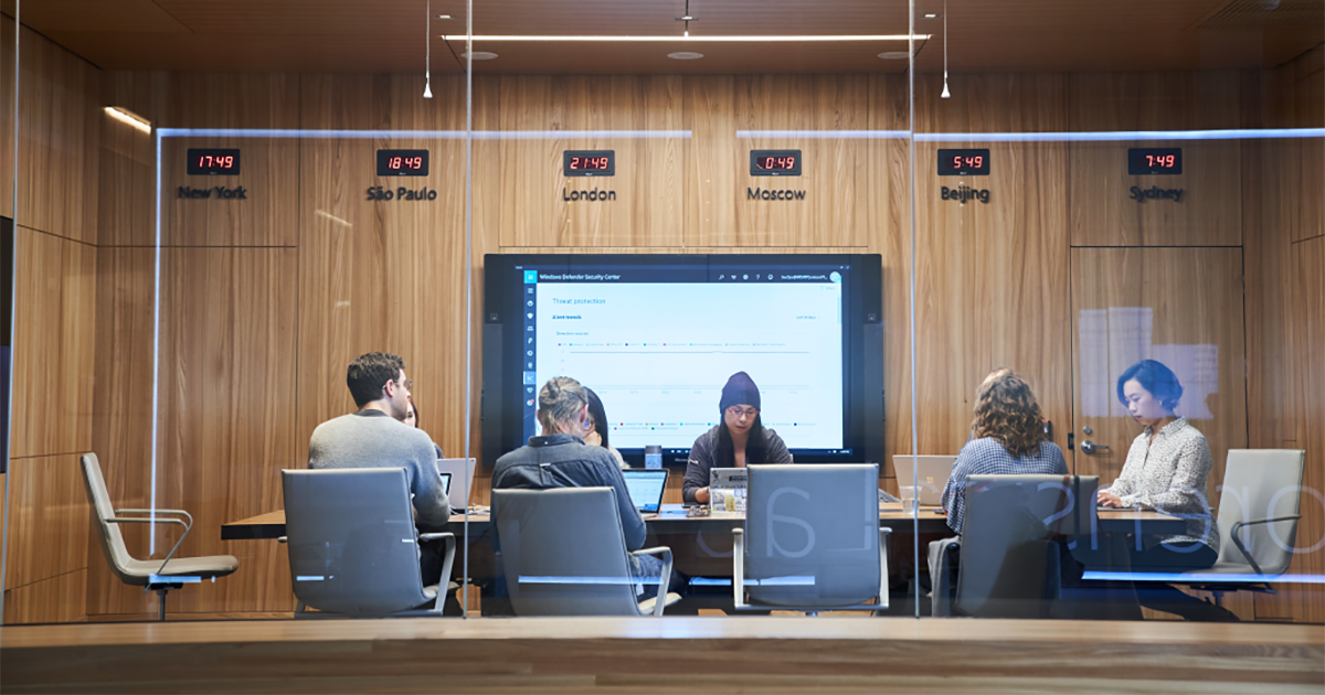 An image of a conference room or board room meeting including people sitting around table in a room with international time clocks.