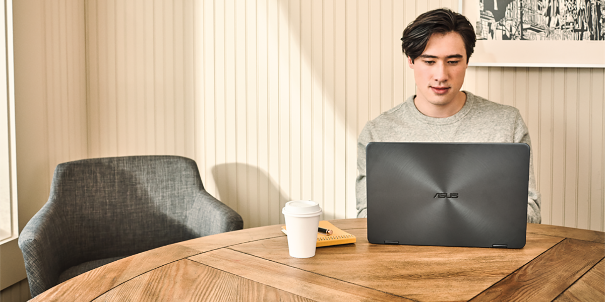 Young man interacting with an Asus Zenbook laptop.