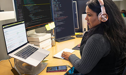 An image of a female developer coding at her desk, wearing headphones.