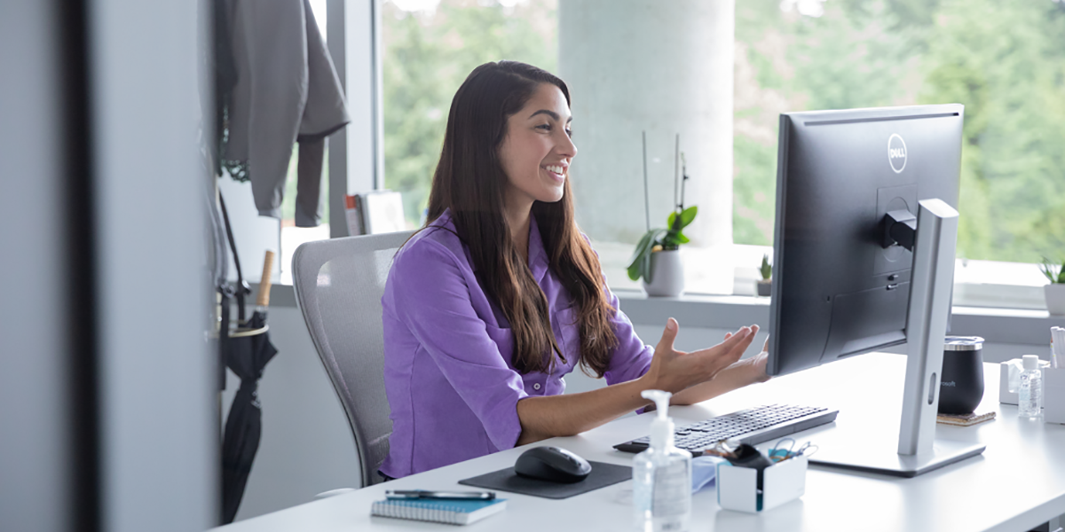An image of a female employee talking on a video call with hand sanitizer on her desk, socially distancing from others.