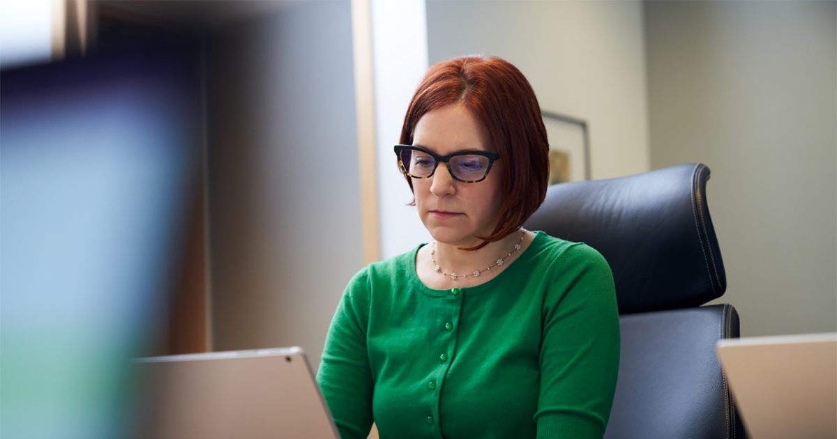 An image of a red-haired woman with a green shirt and glasses, sitting inside an office working on her laptop.