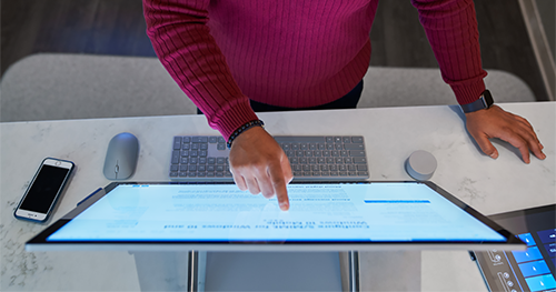 Top down view of a man wearing a dark red shirt working on a Microsoft Surface Studio.