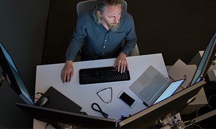 Top-down view of a bearded man in a gray/blue shirt seated at a desk working on a Surface laptop.
