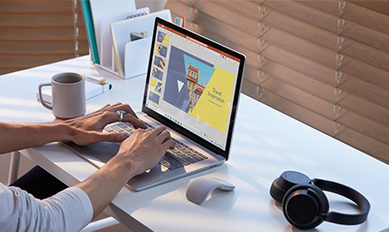 A photograph of Male working on Surface Laptop 3 in PowerPoint with Surface Mouse and Surface Headphones.