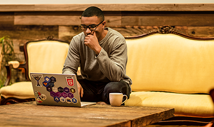 An image of a man sitting on a couch working remotely with his laptop.