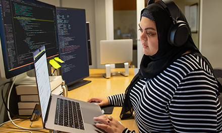 An image of a female developer coding at her desk, wearing hijab and headphones.