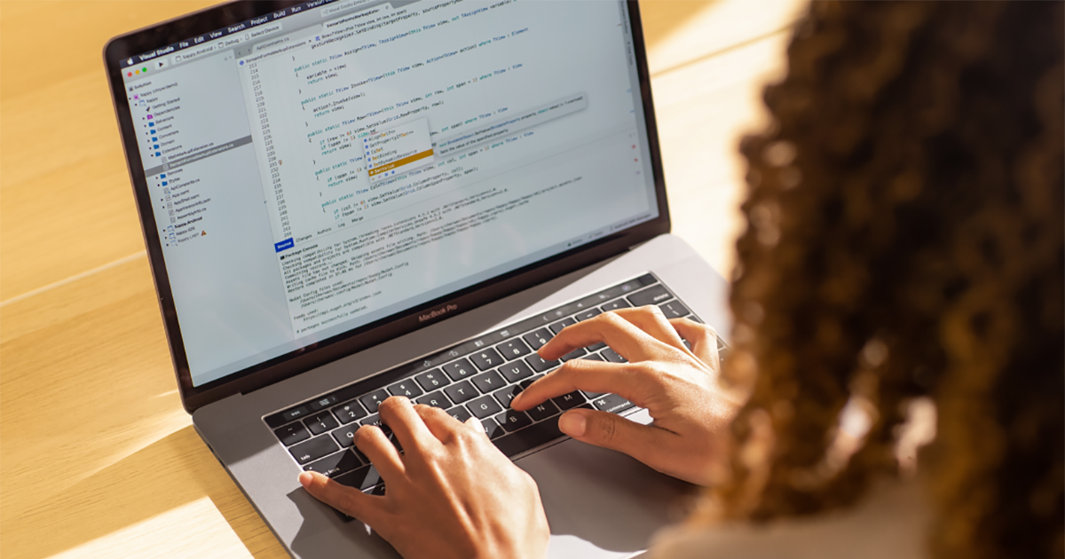 An image of a Black female developer coding on a MacBook Pro in the office, using Visual Studio.