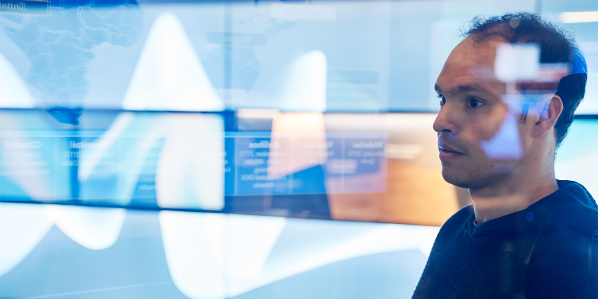 An image of a man in hooded sweater/sweatshirt inside a secure room who is looking at data and a geographic area displayed on a large monitor which is behind glass walls with reflections.