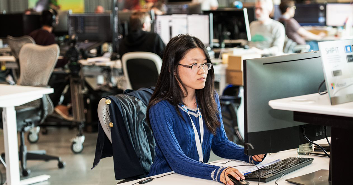 An image of a female developer working at her desk on her computer.