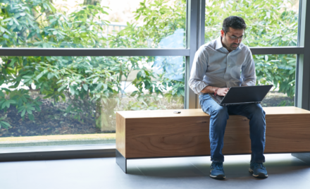 An image of a man sitting on an indoor bench in front of windows working on a laptop with a security key fob or USB drive next to him on the bench.