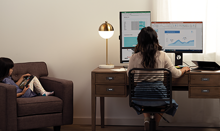 An image of a mother and her daughter are working and learning remotely in their living room.