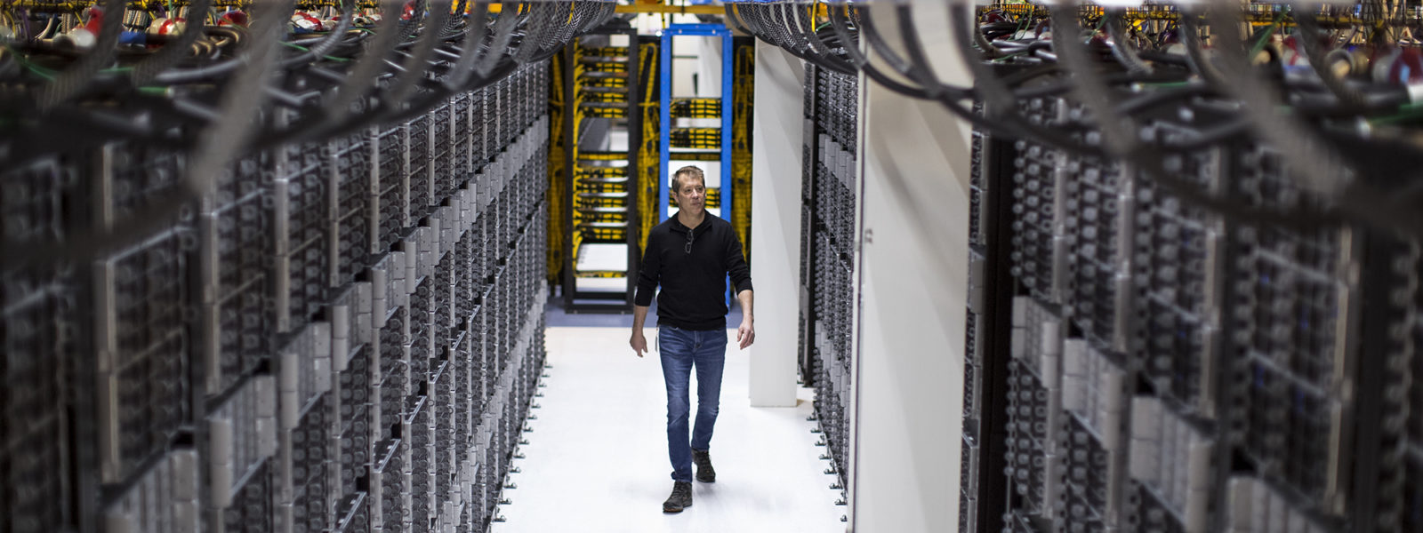 image of a man walking through a State-of-the-art facility uses eco-friendly solutions such as using reclaimed water to cool the data center.